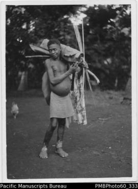 ni-Vanuatu boy carrying various objects including bow and arrow