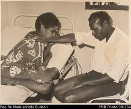 Pastor Silas prays with a patient at the French hospital on the island of Tanna