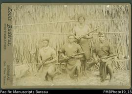 Mounted photograph of four Papua New Guinean armed policemen.