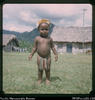 """18. Enga toddler - sing-sing gear. Doctor boys' houses behind, and Tropanda mountain.&..."