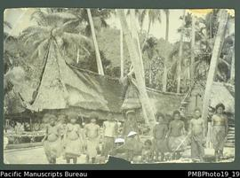 Ten people standing in foreground of Papua New Guinean village, canoe and coconut trees in backgr...