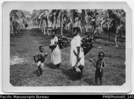 Two ni-Vanuatu women carrying wood and coconut alongside two children