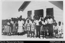 Group of ni-Vanuatu people ouside weatherboard building
