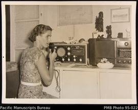 Mrs. Grey operates the tele-radio in the school house, Onesua