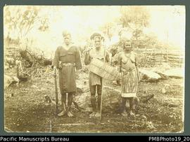 Armed policeman, man with traditional weapons, and woman wearing barkcloth around waist.