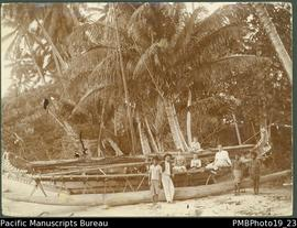 Large outrigger canoe on beach, with three Papua New Guineans and five Europeans.