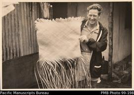 European man holding partially made pandanus mat