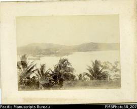 Board-mounted photograph of harbor with ship and European settlement in background. Appears to be...
