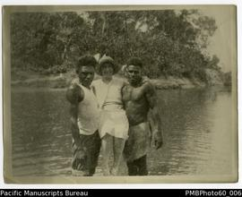 Rita Paton being carried by two ni-Vanuatu men to shore