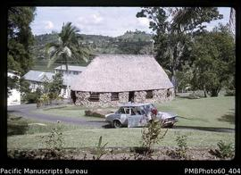 Car parked in front of a thatched building