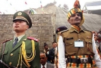 A Chinese and Indian soldier stand side-by-side on parade.