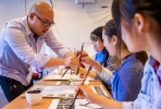 Students try thier hand at Chinese calligraphy. Photo by Tyrone Mason.