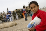 A young girl watches the distribution of humanitarian aid in Kandahar, Afghanistan. Photo by isafmedia on flickr.