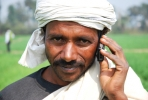 A farmer speaks on his mobile telephone while at work in a wheat field. Photo by CIMMYT on flickr.