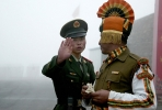 A Chinese soldier gestures while standing alongside an Indian soldier