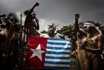 Protesters in traditional costumes displaying the Morning Star flag while demanding recognition of West Papua as an independent nation of Indonesia.  Photo on Google Images, courtesy of Ulet Ifansasti.