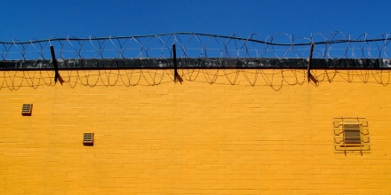 Image of vibrantly yellow wall topped with barbed wire against intensely blue sky.