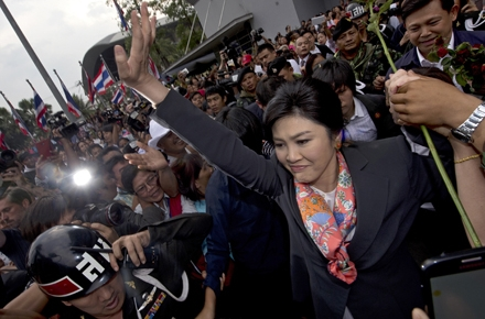 Ousted Thailand Prime Minister Yingluck Shinawatra surrounded by supporters outside the Constitutional Court. Photo by AFP.