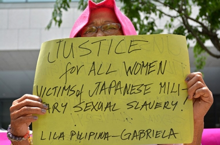 A former 'comfort woman' holds up a placard calling for justice during a standing demonstration near the Diet, or parliament, in Tokyo. Photo by AFP.