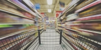 image of supermarket trolley zooming past supermarket shelves