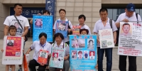Image of people holding up posters with images of missing children