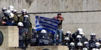 """Photograph: Greek protester unfurls his Greek flag and message, """"Bread, Education, Proximity with politicians, With all necessary sacrifices."""""""