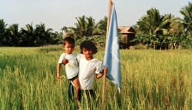 A young girl poses with a United Nations flag in a rice field. Photo by UN Photo