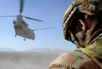 A Special Operations Task Group soldier shields his face from the dust as a CH-47 Chinook aircraft takes off during a mission in Oruzgan. Photo by Department of Defence.
