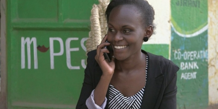 Image of woman using mobile phone to send and receive payments; image by WorldRemit Comms on flickr (CC BY-SA 2.0)