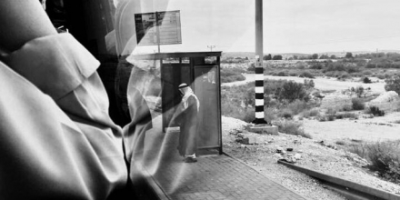 """""""Roaming Charges: A Window Apart"""", (c) Emma Nyhan. Image of a man wearing keffiyeh, at a bus stop in a sparse landscape, taken from a bus window."""