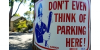 "Image: Sign with cartoon policeman holding truncheon and ""Don't Even Think of Parking Here"" warning"
